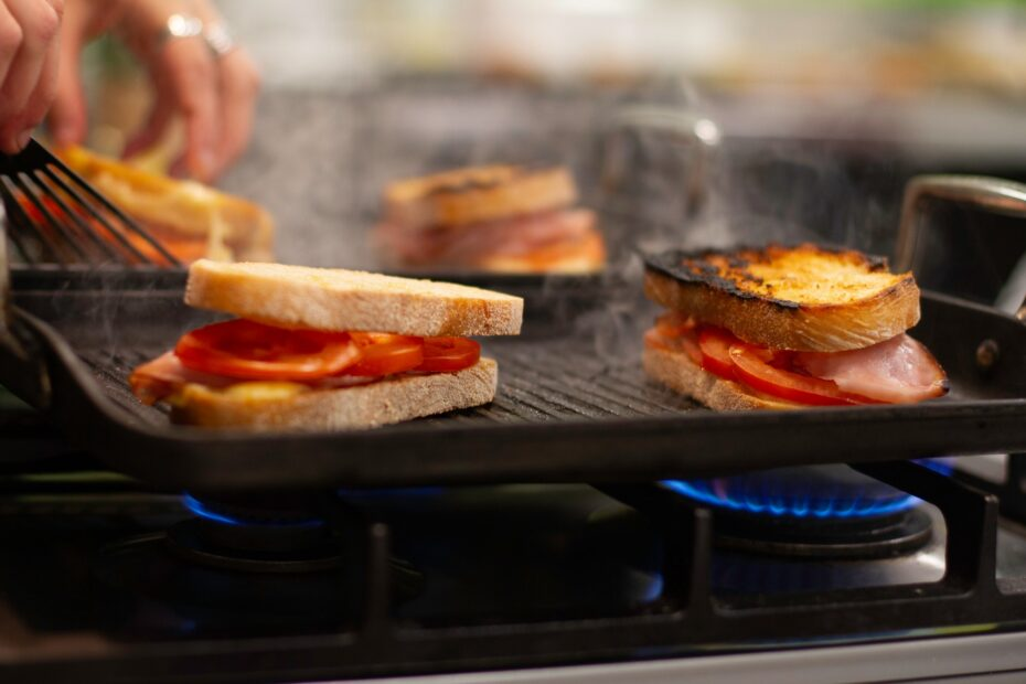 Grilled ham, cheese and tomato sandwiches being toasted on a gas grill/ bbq in the kitchen